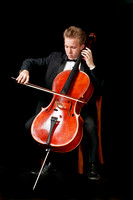 young caucasian cello player with black background